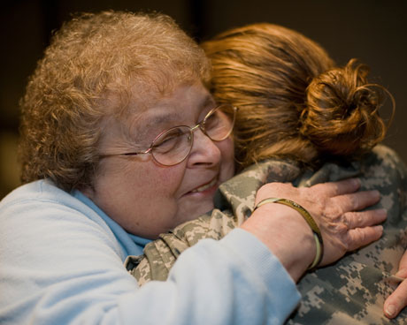 Joan Gaudet gives a hug to a returning troop.